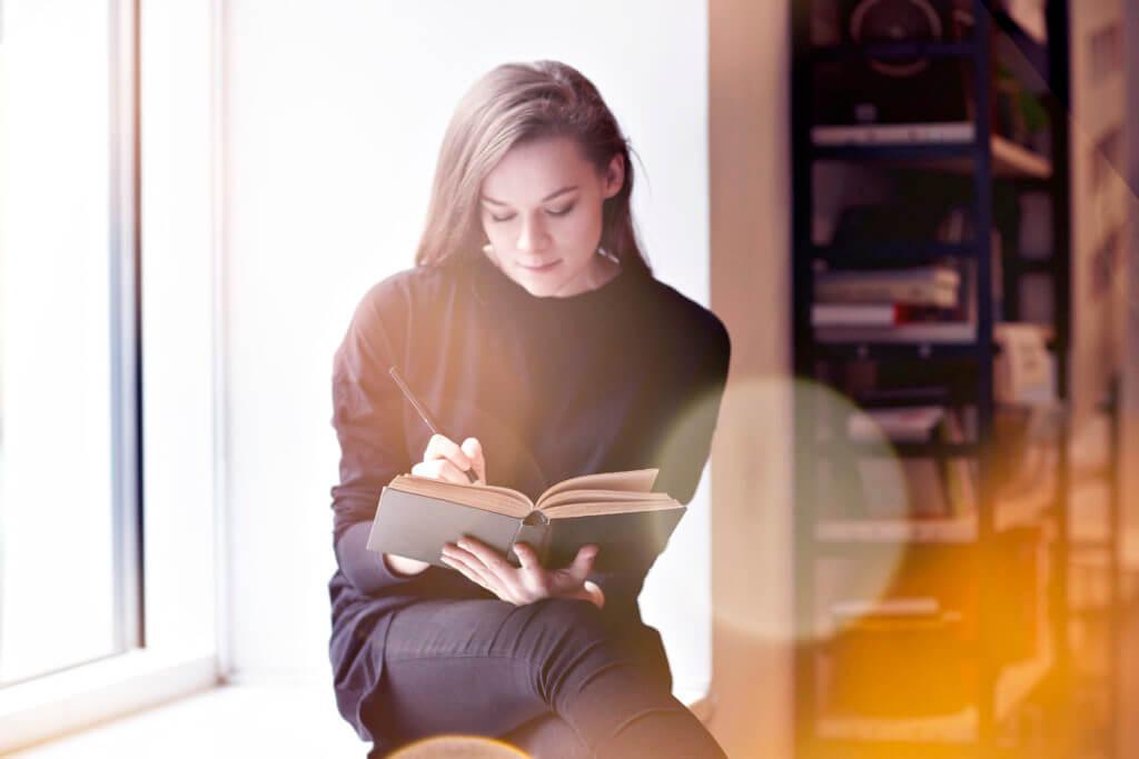 woman writting in book