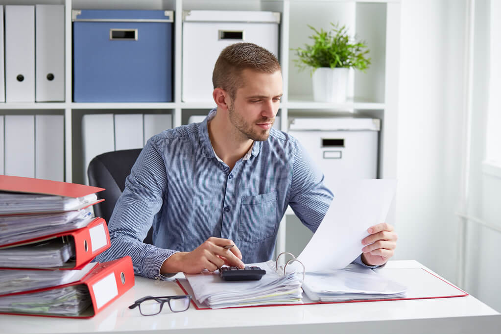 man reviewing document at desk